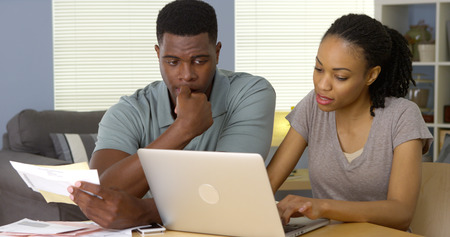 pay bills: Worried young African American couple looking through bills online Stock Photo
