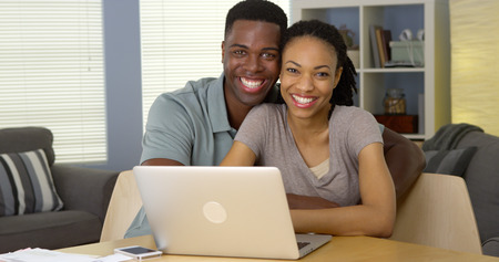 Happy young black couple with laptop and bills Stockfoto