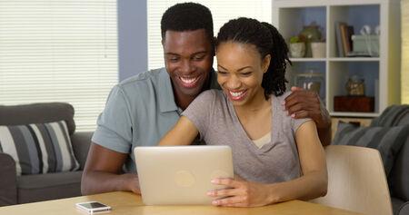 Sourire jeune couple noir agitant et ayant le chat vidéo avec la famille sur la tablette Banque d'images - 33804718