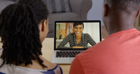 Young black couple talking to friend over laptop video chat