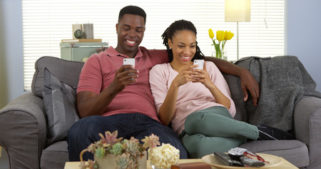 phone: Happy young black couple relaxing on couch using smartphones