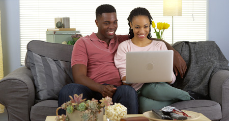 Happy black couple on couch browsing internet with laptop computer Standard-Bild