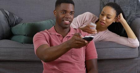 mujer viendo tv: Pareja joven negro sentado en el sof� y sonriendo a la c�mara Foto de archivo