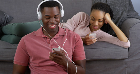 African American couple listening to music and taking picture with smart phones photo