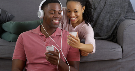 listen music: African American couple listening to music and taking picture with smart phones Stock Photo