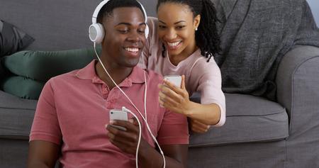 African American paar luisteren naar muziek en het nemen van foto met smartphones