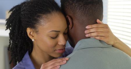 Junge schwarze Paar umarmen und miteinander reden