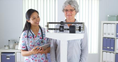 Chinese nurse weighing elderly patient 스톡 콘텐츠