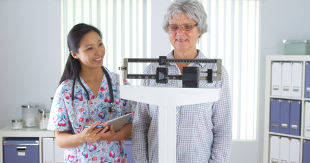 Chinese nurse weighing elderly patient Banque d'images