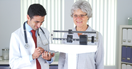 Mexican doctor weighing elderly patient Stock Photo