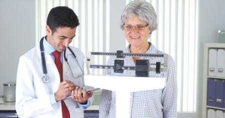 Mexican doctor weighing elderly patient Standard-Bild