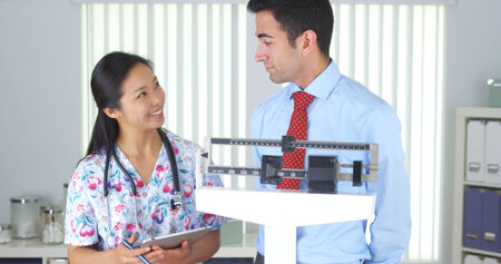 Chinese nurse weighing Mexican patient photo