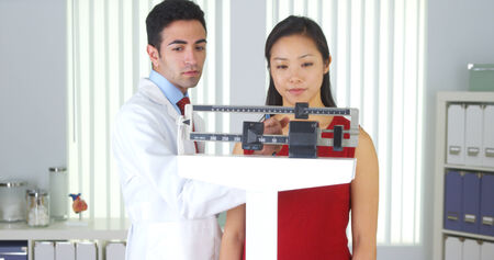 Happy Chinese patient being weighed on scales photo