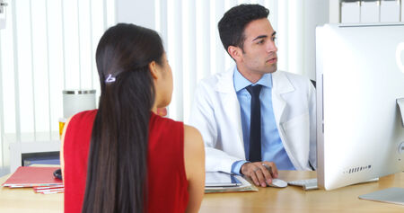 office visit: Hispanic doctor talking with Chinese patient at desk