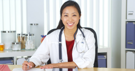 Asian doctor talking to camera at desk Stockfoto