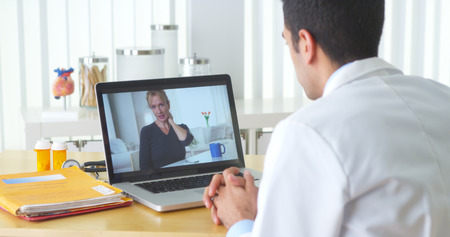 chat: Mexican doctor video chatting with elderly patient Stock Photo