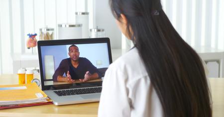 consulta médica: Vídeo médico asiática que charla con el paciente africano Foto de archivo