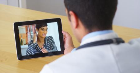 arzt gespr�ch: Hispanic Arzt im Gespr�ch mit junge Frau Patient auf Tablet