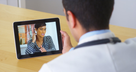 conference call: Hispanic doctor talking with young woman patient on tablet Stock Photo