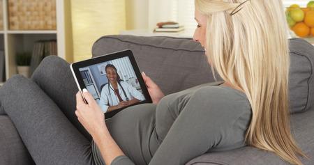 タブレット上の医者に話している妊娠中の女性