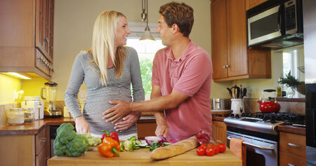 Beautiful pregnant couple cooking in kitchen