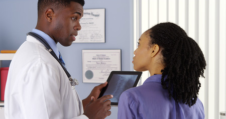 medium shot: African American woman with neck pain talking to doctor about x ray on tablet