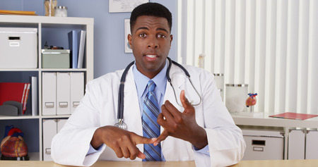 Black doctor talking to camera in video chat