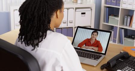 Weibliche Patienten im Gespräch mit African American Arzt über Video-Chat