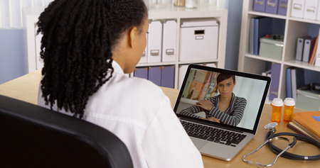 chat: Black patient talking to African American woman doctor over laptop video chat