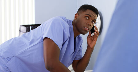 African American male doctor on mobile talking to colleague and using computer photo