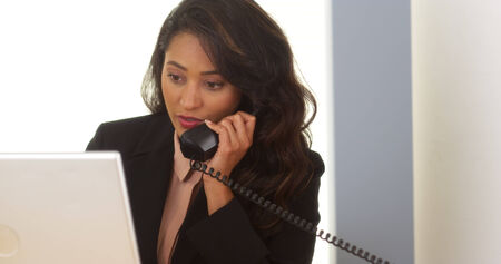answering call: Mexican businesswoman answering phone call Stock Photo