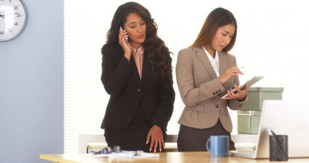 Two mixed race colleagues talking on smartphone and using tablet Stock Photo