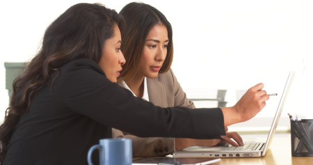 working at office: Multi-ethnic businesswomen doing research at desk