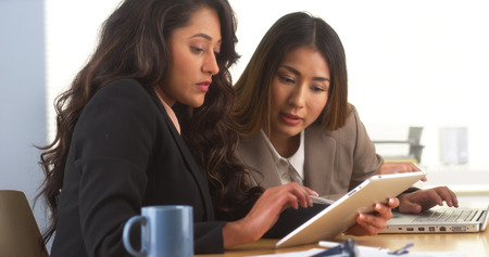 findings: Mexican businesswoman sharing findings on tablet with Japanese colleague Stock Photo