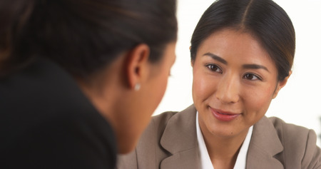 two women talking: Japanese businesswoman talking with Mexican colleague Stock Photo