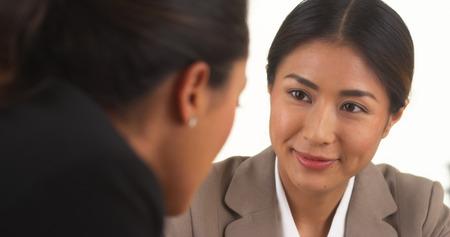 Japanische Geschäftsfrau im Gespräch mit mexikanischen Kollegen Lizenzfreie Bilder