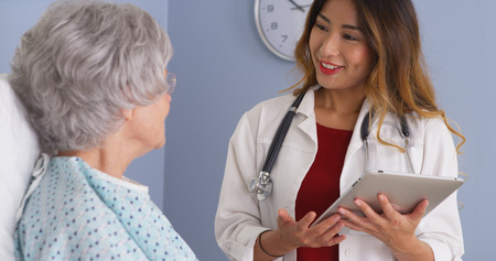 health check: Asian physician using tablet computer talking to elderly woman in bed Stock Photo