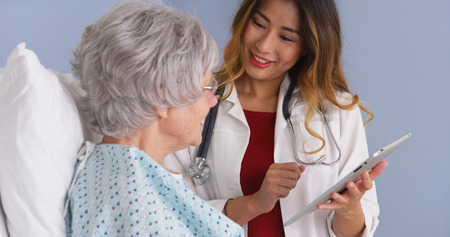 Japanese physician using tablet talking with mature woman patient photo