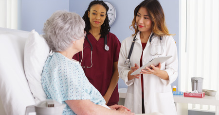 Japanse arts en zwarte verpleegster praten met bejaarde patiënt in het ziekenhuis bed