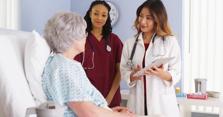 Médico japonés y la enfermera negro habla con el paciente anciana en la cama del hospital