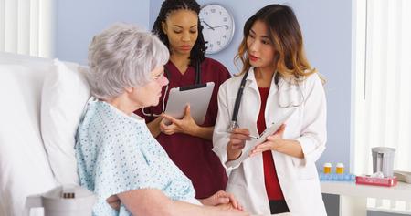 Médecin asiatique et afro-américaine infirmière parlant à personne âgée dans une chambre d'hôpital Banque d'images - 33805006