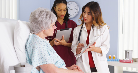 Asian doctor and African American nurse speaking to elderly patient in hospital room