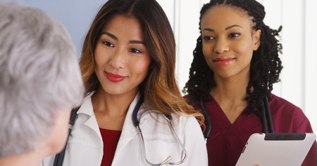 Asian woman physician and black nurse with elderly patient
