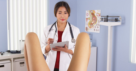 Asian OBGYN examining pregnant patient photo