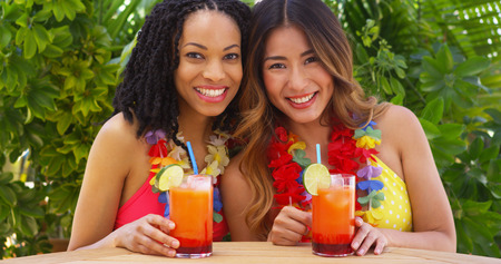 Black and Asian best friends enjoying tropical vacation together photo