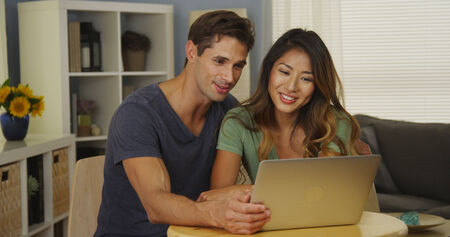 Interracial couple video chatting with family on laptop photo