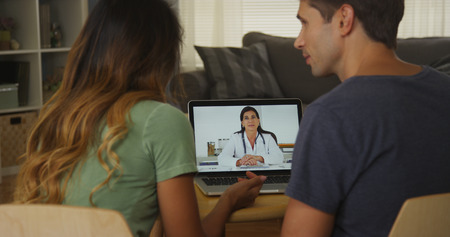 Interracial couple talking with doctor on laptop