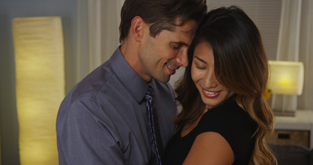 Sweet interracial couple hugging photo