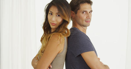 Mixed race couple standing back to back photo