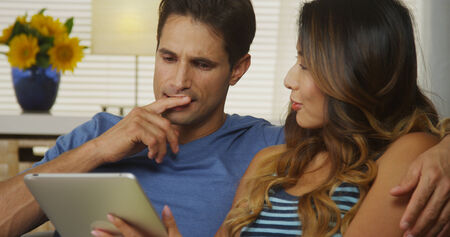 Mixed race couple using tablet together photo